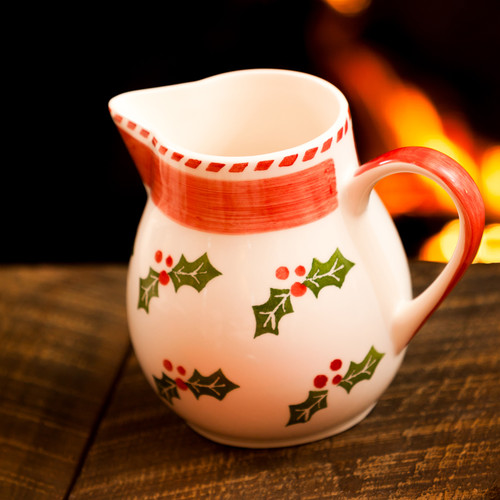 a round pitcher featuring a holly and berry design, a large red stripe, and a red handle sitting on a wooden table in front of a  lit fireplace