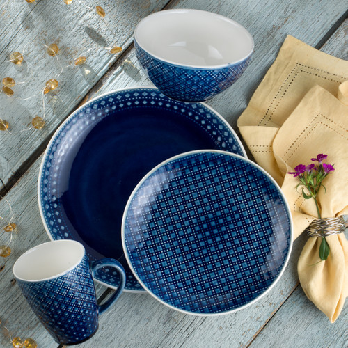 place setting of a blue crackle glaze dinnerware set on a grey background with yellow napkin