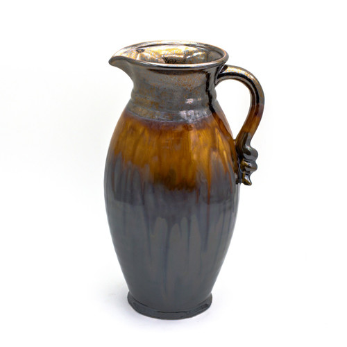 metallic decorative pitcher with coppery lip, stripe of brown dripping crackle glaze, reflective metallic bottom and a swirled decoration on the handle