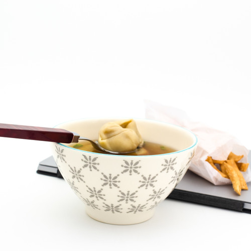 a single white bowl with grey patterns filled with chinese takeout with a laptop in the background