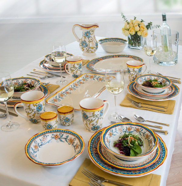 a formal table laid with ornate gold and turquoise dinnerware and range of accessories on a starch white tablecloth with yellow napkins and a yellow floral arrangement