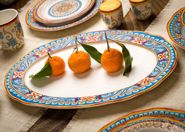 an ornately decorated oval platter with a scalloped lip and a gold and turquoise floral design sits on a dark wooden table and several pieces of dinnerware cut out of the frame. three oranges sit on the platter