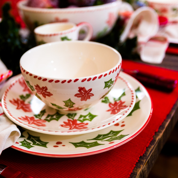 place setting of dinnerware featuring a holly and berry design set on a wooden table with red place mats and several accessory pieces in the background