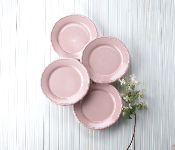 four pink salad plates on a grey background with a flower