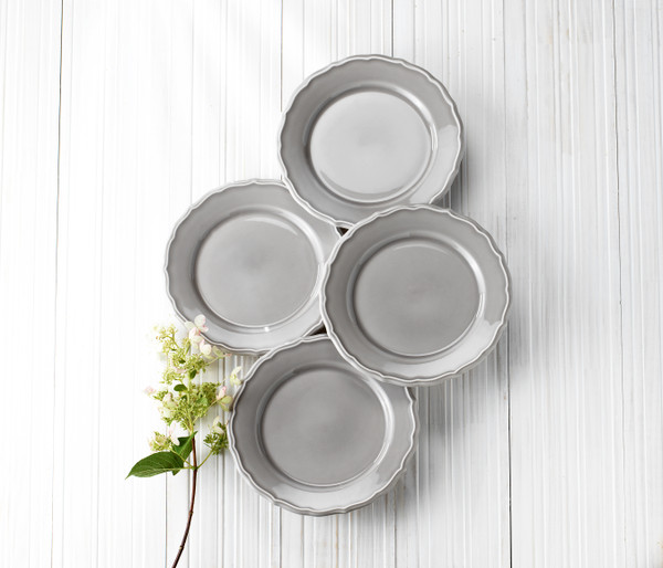 four grey salad plates on a grey background with a flower