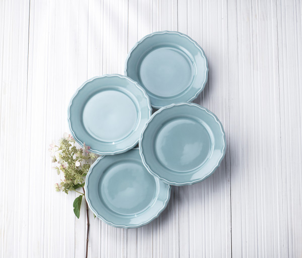 four blue salad plates on a grey background with a flower