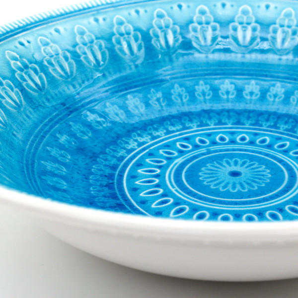 detail view of serving bowl in turquoise with crackle glaze and a traditional mandala design.