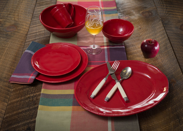 lifestyle view of several pieces of red dinnerware plus oval platter and serving bowl with beaded detailing around the rims. the plates are laid on a warm wooden table with plaid table runner. the photo is propped with a wine glass, silverware, and a single apple.