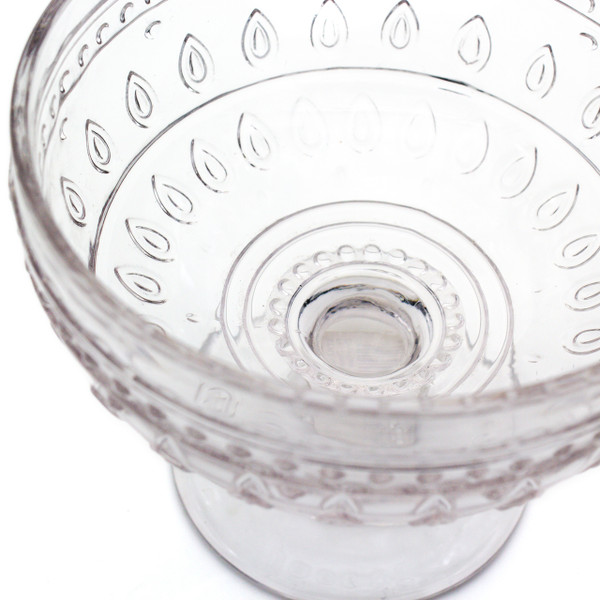 close up of a single clear compote glass with embossed teardrop and mandalas