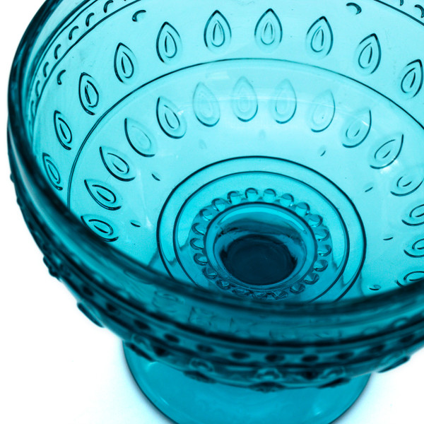 close up of a single turquoise compote glass with embossed teardrop and mandalas