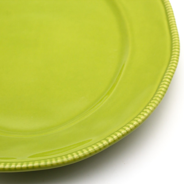 detail view of a green oval platter with beaded accents around the rim