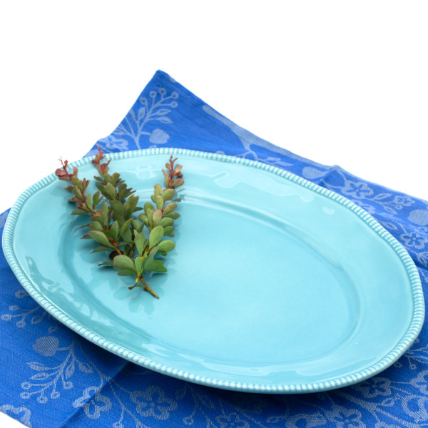 blue oval platter with beaded accents around the rim with several herb sprigs resting on it and a blue cotton place mat underneath