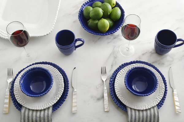 lifestyle of a beaded rim dinnerware set in mixed blue and white accented with limess and a striped napkin