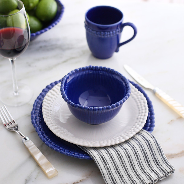 lifestyle of a beaded rim dinnerware set in mixed blue and white accented with limes and a striped napkin