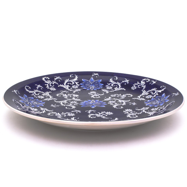 side view of a dark blue large decorative plate with hand-painted lotus design