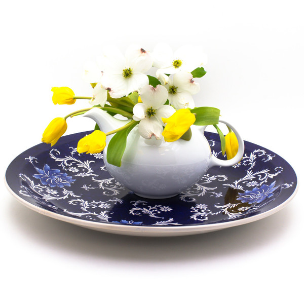 lifestyle view of a dark blue large decorative plate with hand-painted lotus design. a white teapot containing a bouquet of yellow tulips and dogwood sits in the middle of the plate