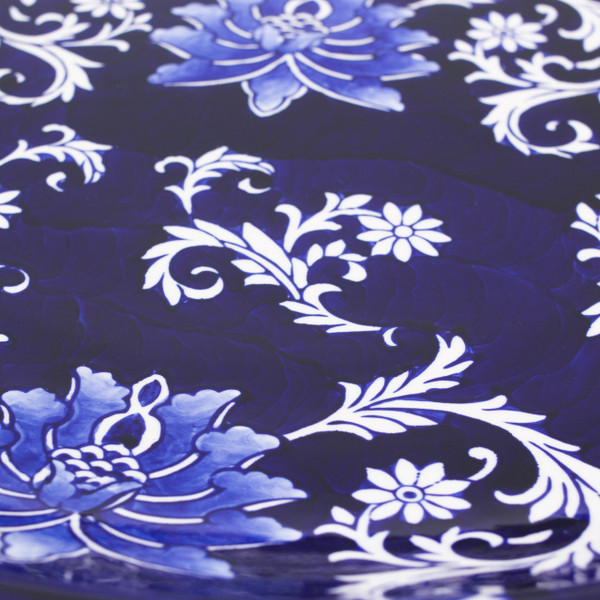detail view of a dark blue large decorative plate with hand-painted lotus design showing the individual brush strokes and detail in the design