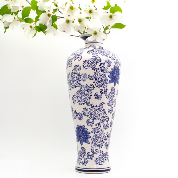 lifestyle view of a tall vase with a white body and hand-painted blue lotus pattern featuring a large dogwood branch in the vase
