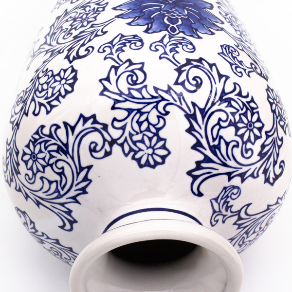 detail view of a tall vase with a white body and hand-painted blue lotus pattern showing the brushwork