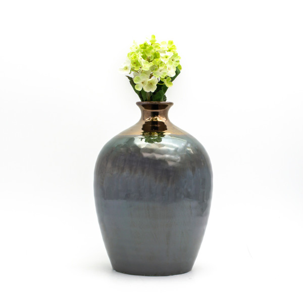 lifestyle shot of small round metallic vase with a copper mouth and a greenish body featuring a small bouquet of yellow artificial flowers