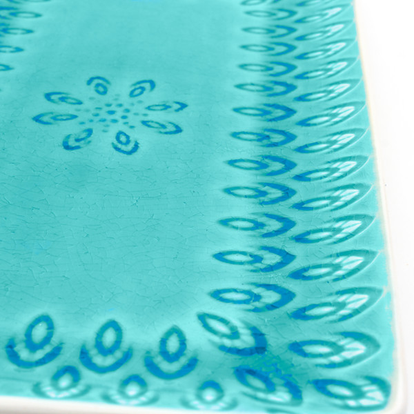 detail view of lagoon rectangular platter with crackle glaze and an embossed peacock feather design
