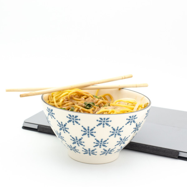 a single white bowl with blue patterns filled with chinese takeout with a laptop in the background