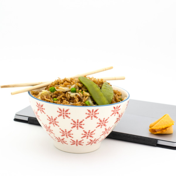 a single white bowl with red patterns filled with chinese takeout with a laptop in the background