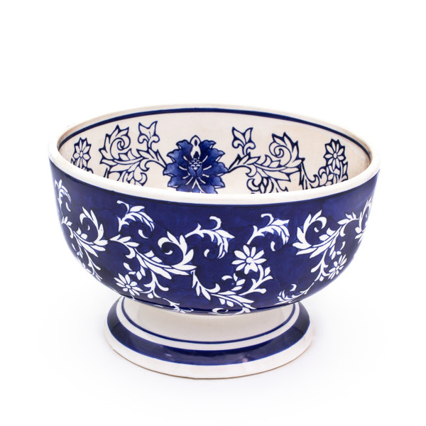 a small footed bowl with dark blue exterior and white interior decorated with a hand-painted lotus design.