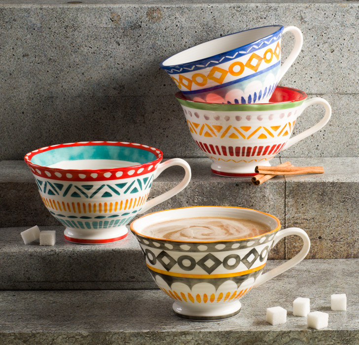lifestyle of four large latte mugs with assorted colors and geometric patterns. the mugs are set on stone steps and one contains a cappuccino with several sugar cubes scattered around