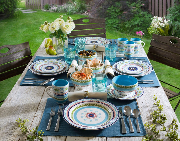16 piece dinnerware set with a blue and green design set on a grey table outdoors with green-blue place mats
