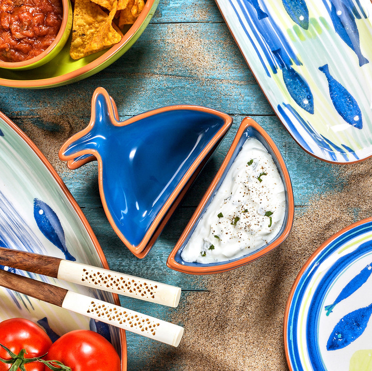 assortment of fish themed dining accessory pieces on a sandy blue background with fish net and shells as decoration