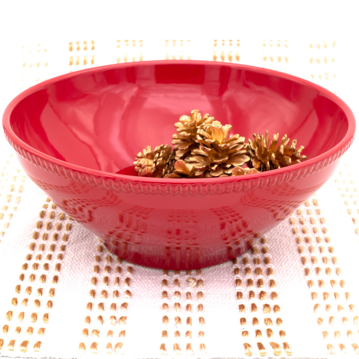 a large red serving bowl with beaded accents around the rim filled with pine cones and set against a background of white and gold stripes