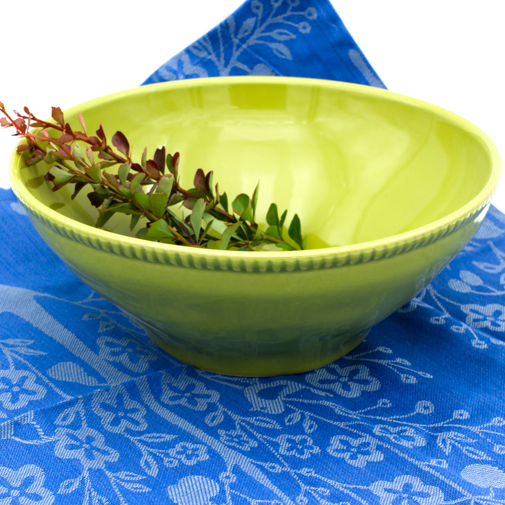 a large green serving bowl with beaded accents around the rim filled with herbs and placed against a background of blue cloth