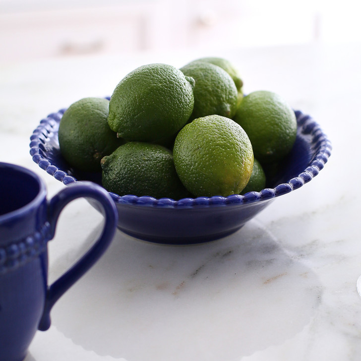 lifestyle of wide lipped blue bowl with beaded rim filled with limes