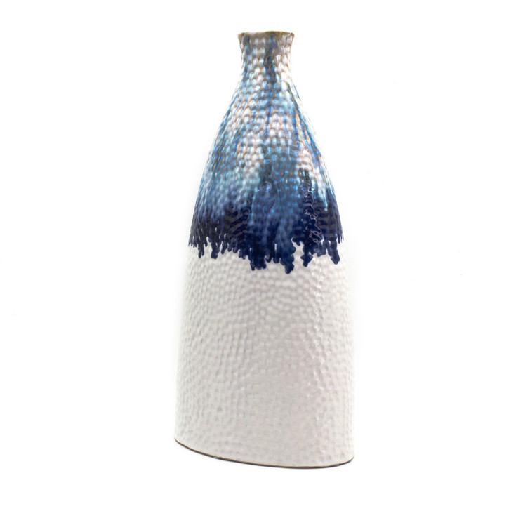 Slightly angled view of a flattened shoulder vase. The vase features shades of blue glaze dripping from the top that transition to a flat white. The vase is marked all over with small indents like sand that has been brushed by the tide.