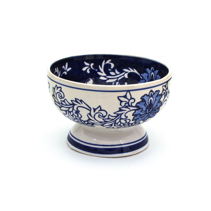 a small footed bowl with white exterior and dark blue interior decorated with a hand-painted lotus design.