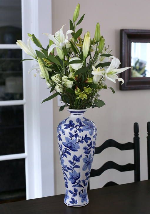 lifestyle view of tall white vase with hand-painted  vine and floral design featuring a large lily bouquet in the vase
