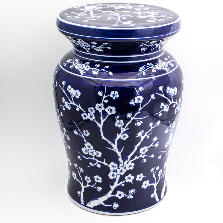 angled view of cobalt garden stool featuring a hand-painted cherry blossom design. the stool has a narrow neck and wide flat podium top with a curved body showing more of the top of the stool