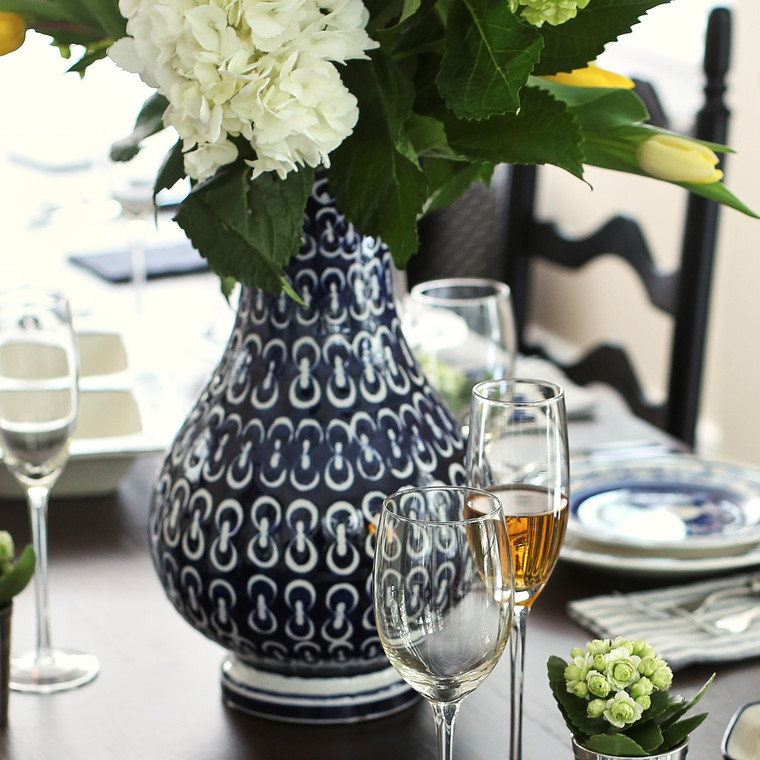Lifestyle of Round and curvy vase with wide lip and blue-and-white hand-painted chain design featuring large hydrangea blooms in the vase. set on a formal dinning table