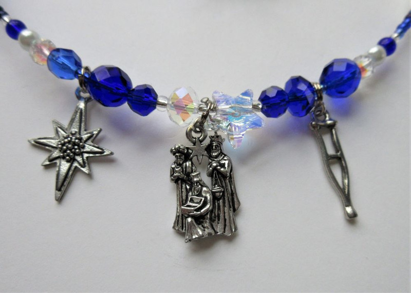 Charms on the bracelet include Amahl's crutch, the Magi and Christmas star.