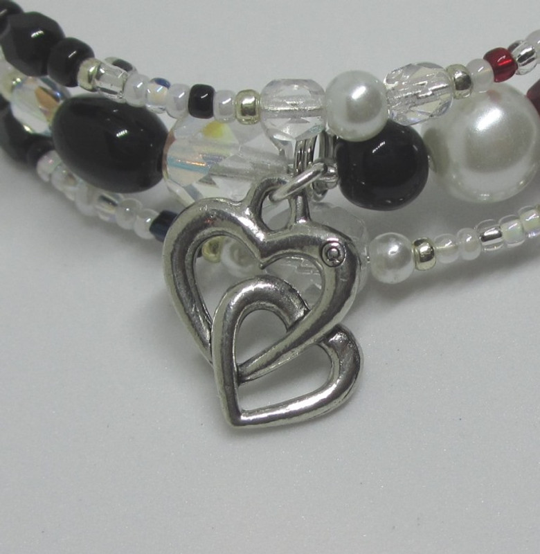 The entwined hearts charm symbolizes lovers Nedda and Silvio
