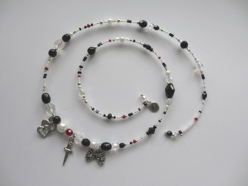 White and black beads represent the colors of Pagliaccio in the traditional Commedia dell'arte costumes so often utilized in costumes for the opera Pagliacci..