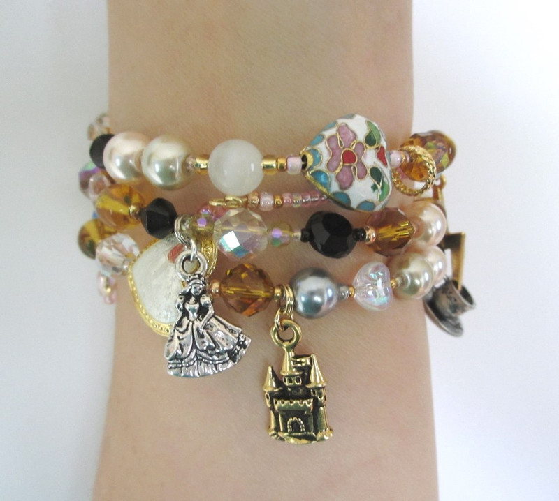 Wrist view of the Cenerentola Bracelet highlighting the cloisonne beads, princess and castle charms.