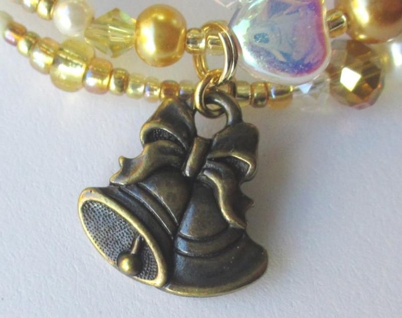 A bell charm, along with tiny bells on the bracelet,  evoke Zuzu Bailey's recollection that every time a bell rings an angel gets its wings.