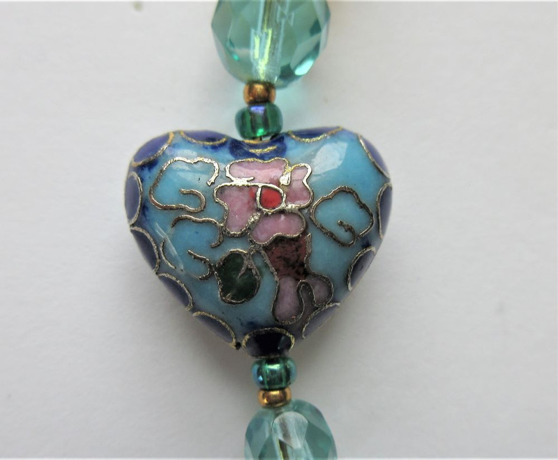 A cloisonne heart bead (center) represents the love of the Prince and Rusalka.