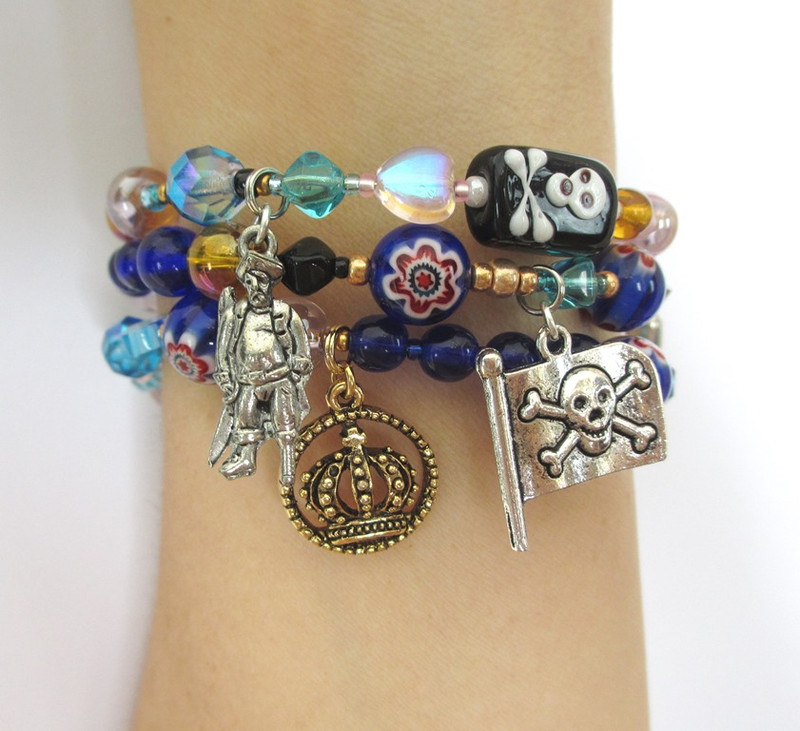 Wrist view of the Pirates of Penzance bracelet featuring the Pirate King, crown charm and Pirate Flag.