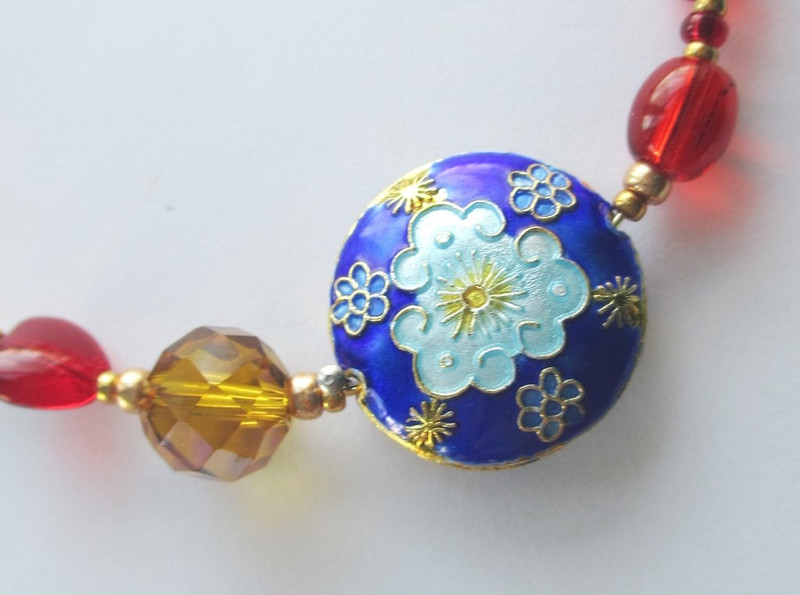 A large gold crystal symbolizes the Mikado, Emperor of Japan. A large round bead with a sunburst represents the joy of the towns people at the end of the operetta.