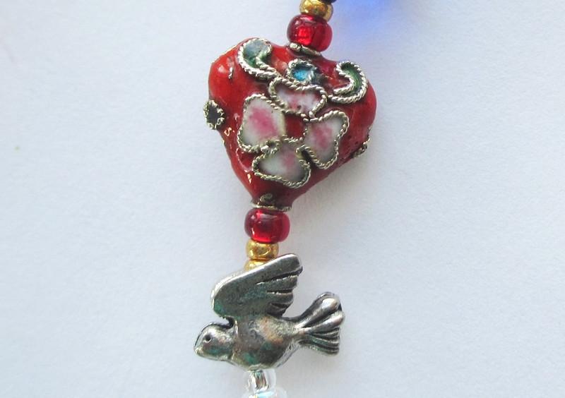 A red heart and tiny bird bead evoke Ko-Ko's love song to Katisha