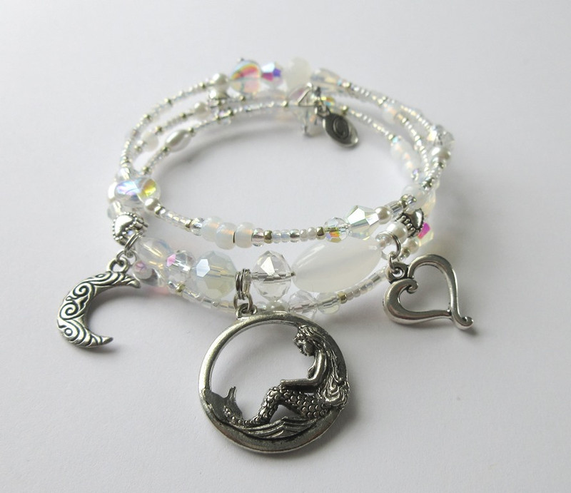 "Opalescent and Iridescent crystals and hearts and tiny glass pearls give a ""lunar glow"" to the bracelet."