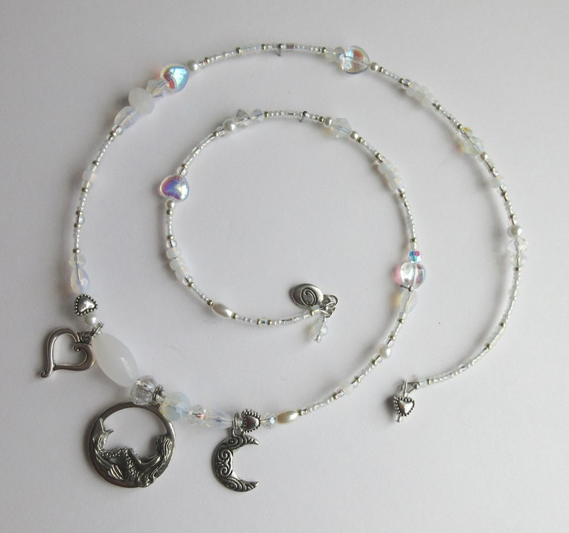 "Iridescent crystals and hearts along with tiny glass pearls complete the ""lunar glow"" of the Song to the Moon bracelet"
